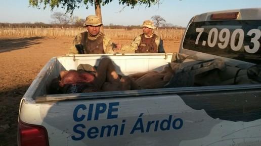Policiais observam os corpos dos assaltantes